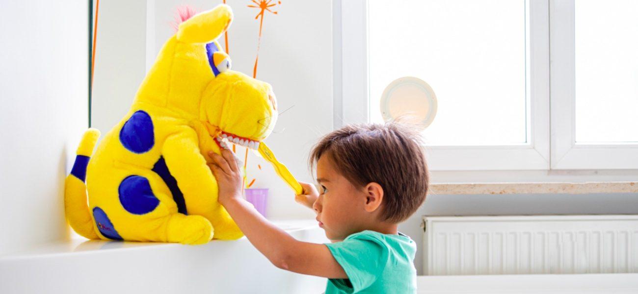 Kind übt Zähneputzen an Kuscheltier